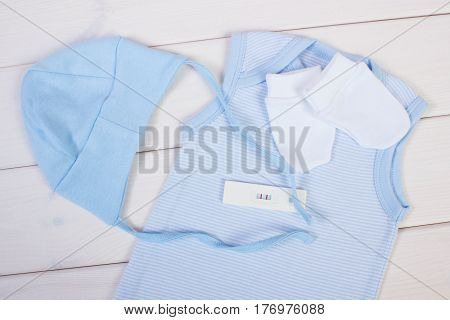 Pregnancy Test With Positive Result And Clothing For Newborn, Expecting For Baby