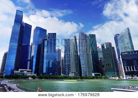 Singapore, Singapore - February 10, 2017: People walk and relax alongside the Singapore river near skyscrapers on sunny day in Singapore.