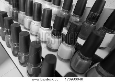 Set of different bottles of nail polish in the shelf in the beauty salon