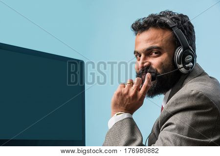 Closeup portrait of Indian bearded young man in suit, indoor, listening to headphones, browsing digital computer laptop, asian man in call center