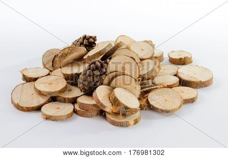 Pile of little round pieces of sawn pine branches and two pine cones on white background