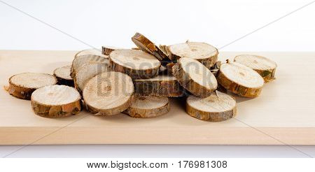Pile of little round pieces of sawn pine branches on wooden plank on white background