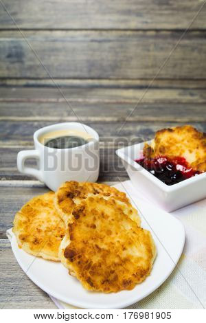 Cheese pancake with coffee and jam on the wooden background with copy space