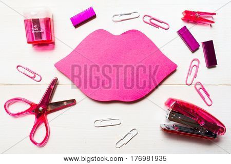 Different pink stationary on the white wooden table with copy space