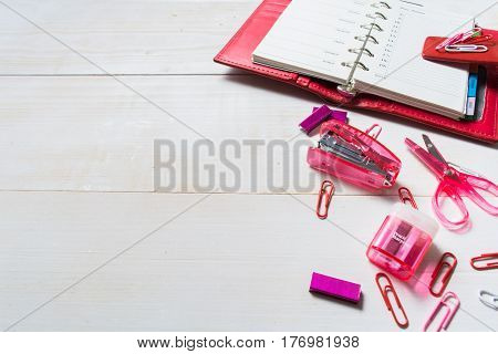 Planning concept for girl or woman with red organizer and pink stationary on the white wooden table