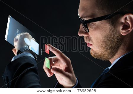 business, people, communication and modern technology concept - close up of businessman with smartwatch and incoming call virtual projection over black background