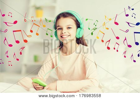 people, children, rest and technology concept - happy smiling girl lying awake with smartphone and headphones in bed listening to music at home