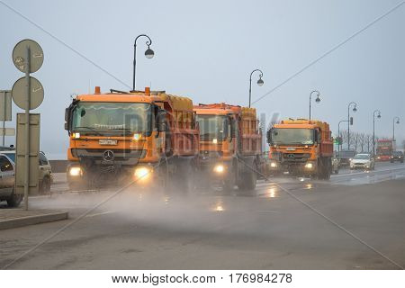 ST. PETERSBURG, RUSSIA - MARCH 12, 2017: Trucks of city municipal services on cleaning of the embankment in the foggy spring afternoon