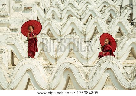Myanmar Novice monks are playing on the white pagoda and holding red umbrella