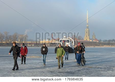SAINT PETERSBURG, RUSSIA - MARCH 12, 2017: Employees of EMERCOM of Russia on the rescue ship Khivus-20 forbid people to go out on the melted ice on the frozen Neva river on a March day