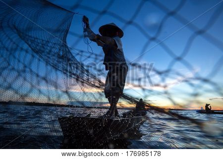 Thai fisherman on wooden boat casting a net for catching freshwater fish in nature river in the early evening before sunset