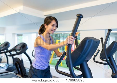 Young Woman training on Elliptical machine