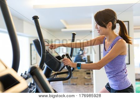 Woman training on Elliptical machine and touch on panel in gym