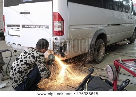 Kaluga, Russia - March, 15, 2017: Worker works with angle grinder in a car repair shop in Kaluga