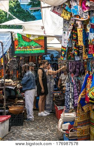 Cape Town South Africa - March 02 2017: Toutists shopping for African products at colourful stalls at Greenmarket square in Cape Town.