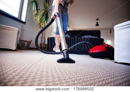 woman vacuuming carpet in living room - focus on the head of hoover