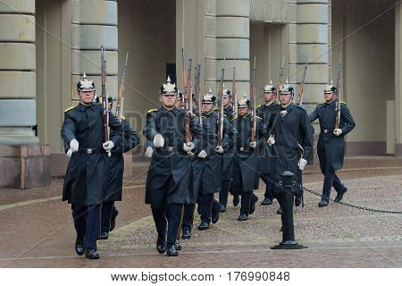 STOCKHOLM, SWEDEN - AUGUST 29, 2016: Royal guardsmen march at the palace in the rainy afternoon