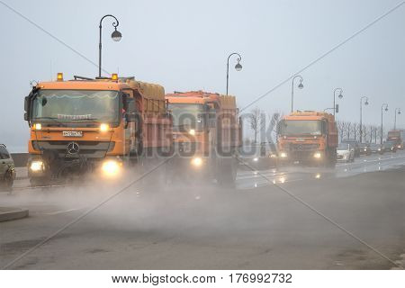 ST. PETERSBURG, RUSSIA - MARCH 12, 2017: Cars of city municipal services wash Palace Embankment in the foggy March afternoon