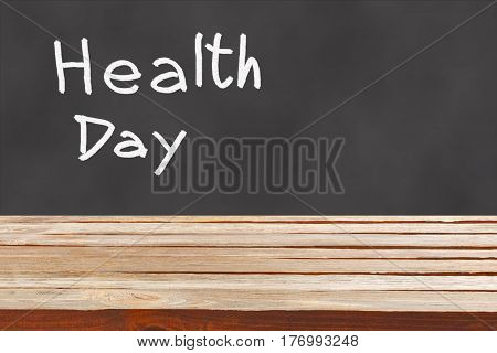 Empty wooden table in front of black chalkboard with an inscription Health Day written in white chalk. World Health Day concept.
