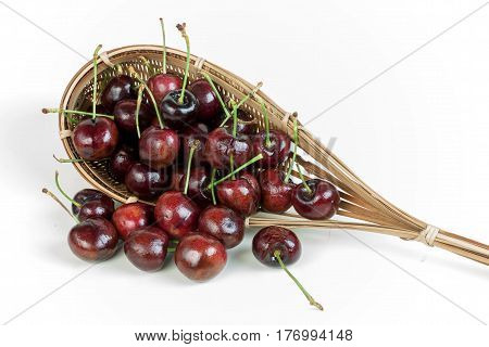 cherries stack in fruit-picker made of a wicker scoop fixed to long handle on white background.