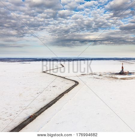 Aerial view of oil rig at an oil field in Western Siberia in the winter day. The deposit of oil and gas in the tundra of Yamal, Russia.