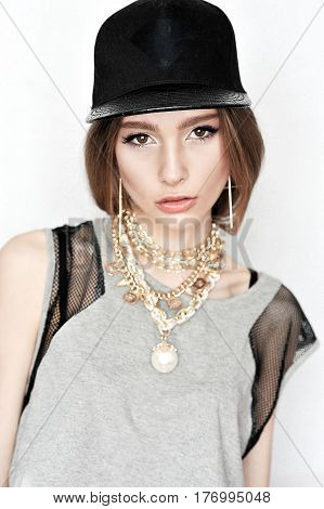 High fashion look.glamor stylish beautiful young woman model with pale lips in hipster gray cloth in cap Girl having fun
