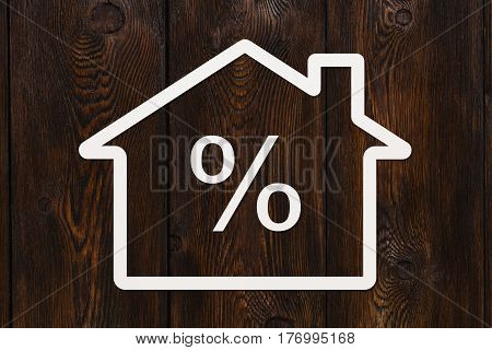 Paper house with percent sign inside on wooden background. Mortgage credit concept. Abstract conceptual image