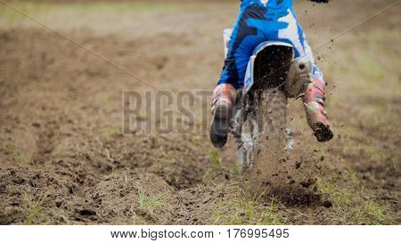 Motocross racer start riding his dirt Cross MX bike kicking up dust rear view, close up, telephoto