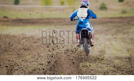 Motocross racer start riding his dirt Cross MX bike, telephoto