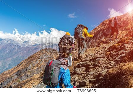 Group of People walking up on steep Mountain Trail using Hiking Gear carrying Backpacks Sun shining