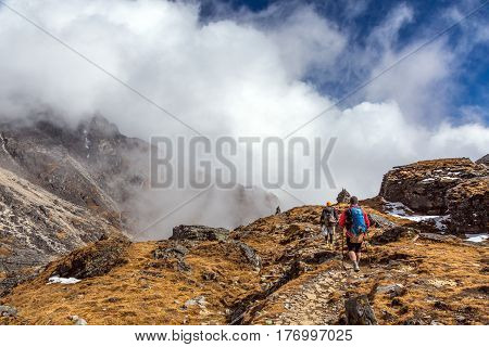 Two Mountain Hikers walking on Trail with mixed rocky and grassy surface carrying Backpacks using walking Sticks massive Clouds in Valley on Background