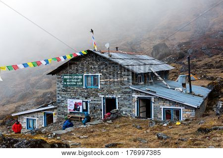 Mountain Hut in Nepal Himalaya Mountains on Mera Peak trek. Stone Building with traditional buddhist prayer flags at foggy weather. Thuli Kharka Lodge, Solo-Khumbu region, Nepal, November 1, 2016