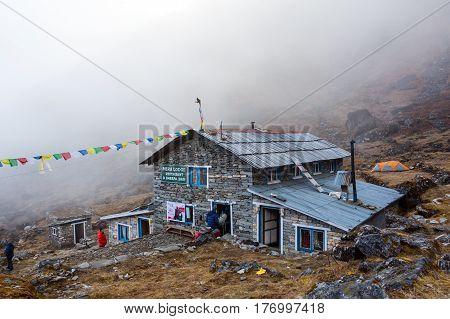 Mountain Hut in Nepal Himalaya Mountains on Mera Peak trek. Stone Building decorated by traditional buddhist prayer flags foggy weather. Thuli Kharka Lodge, Solo-Khumbu region, Nepal, November 1, 2016