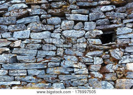 Stone Wall of rural Building made with manual work without linking solution of small pieces of rocks carefully tailored to each other with small empty Window.