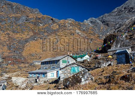 Mountain Hut in Nepal Himalaya Mountains. Group of stone Buildings decorated by traditional buddhist prayer flags and View of high rocky Pass on Background