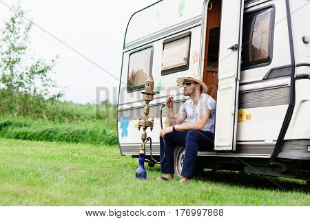 Young, handsome hipster smoking hookah outdoors. Holiday, vacation, trip concept.