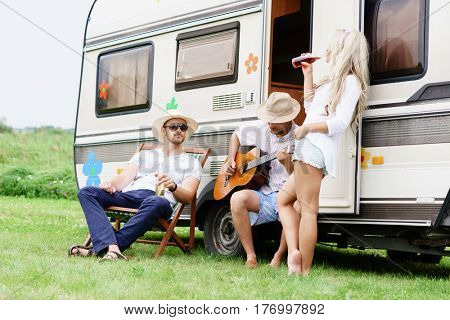 Happy friends having a good time together outdoors. Chatting, drinking, playing guitar. Friendship, spare time, holiday concept.