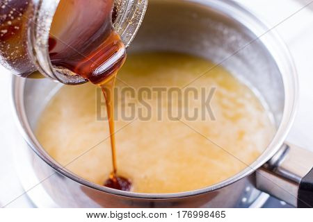 Pouring liquid honey in a bowl on a wooden background