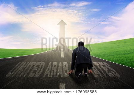 Male manager kneeling on the road with United Arab Emirates word while looking at road shaped upward arrow