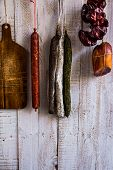 Charcuterie variety of sausages hanging on hook wood cutting board string with dry peppers nyora Spanish meat delicacies pantry poster