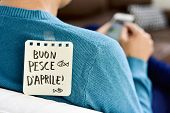 closeup of a young caucasian man seen from behind using his smartphone, with a note with the text buon pesce d aprile, happy april fools day in italian, attached with tape to his back poster