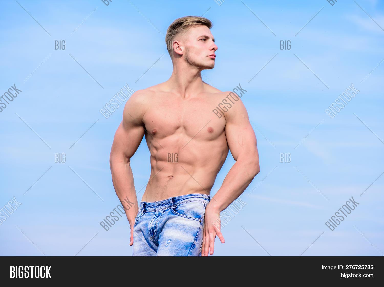 b6ec2d4ce61 Muscular masculine guy look confident. Man sexy muscular bare torso stand  outdoor blue sky background. Man muscular torso stand confidently.