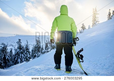 Back View Of Snowboarder Climbing With His Board On The Mount For Backcountry Freeride Session In Th