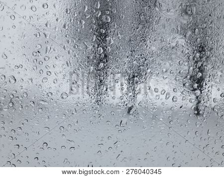 View Through Water Drops On  A Weeping Car Window On Trees In Winter Season