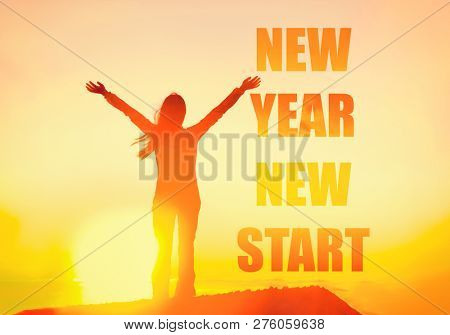 New Year 2019 New Start motivation inspirational quote message on silhouette of winner woman in sunset with arms up in happiness. You can start to change your life.