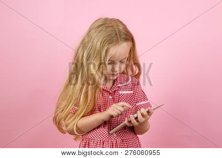 Shopping Smart. Little Girl Shopping On Smartphone. Little Shopaholic Shopping Online. Small Girl In