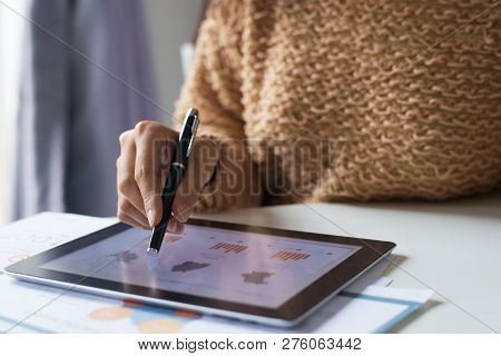 Close-up Of Busy Woman Analyzing Statistics While Using Tablet. Unrecognizable Lady In Sweater Sitti