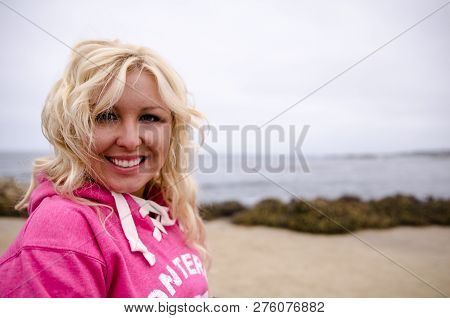 Beautiful Blonde Woman With Beach Waves And Touseled Hair Stands And Poses On A Windy Beach Along Th