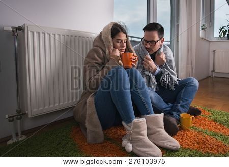 Young Couple In Jacket And Covered With Blanket Sitting On Floor Beside Radiator And Trying To Warm