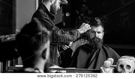 Hipster Client Getting Haircut. Barber With Hair Clipper Works On Hairstyle For Man With Beard, Barb